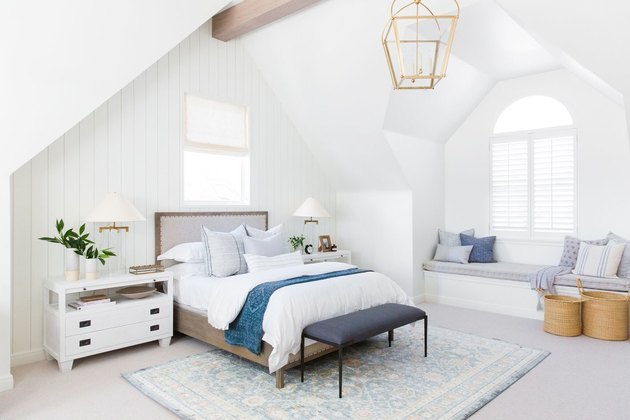 farmhouse style bedroom with white walls and gold chandelier