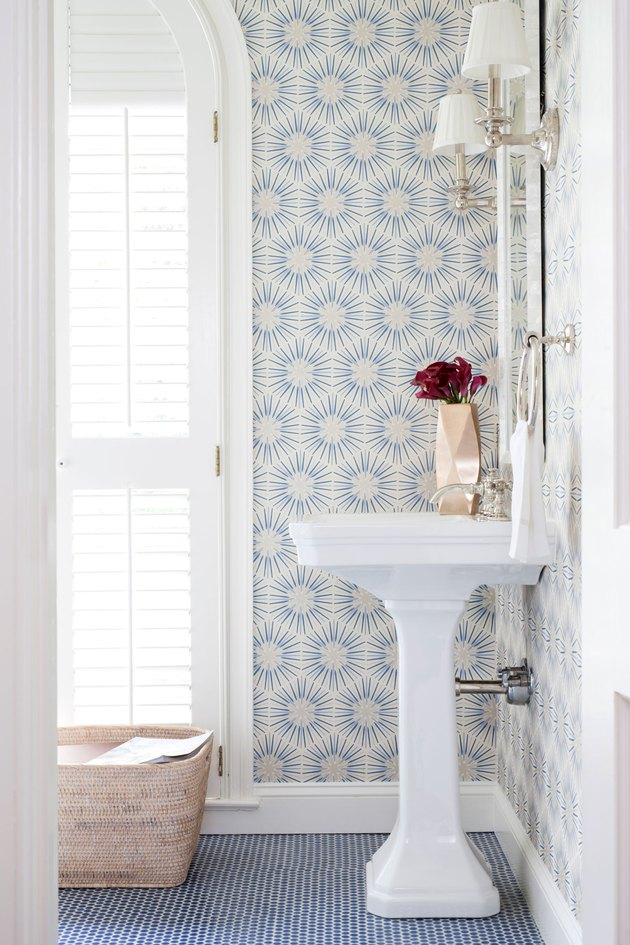 half bathroom idea with blue mosaic tile flooring and patterned wallpaper