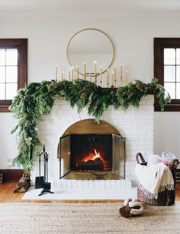 rustic white fireplace with wood panels and brass detailing