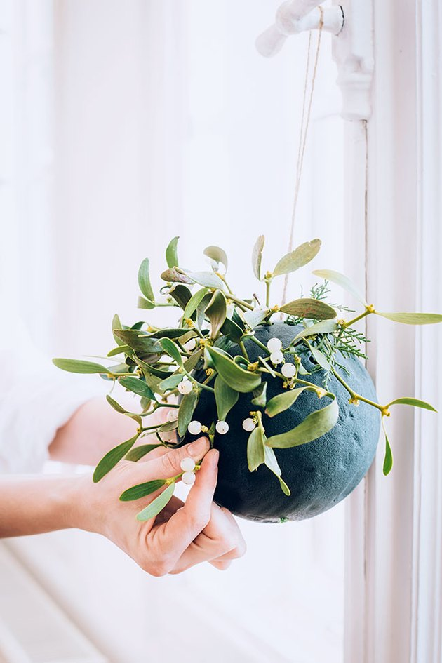 Add greenery to kissing ball