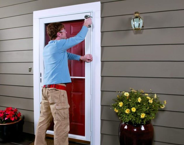 Man attaching door to trim.