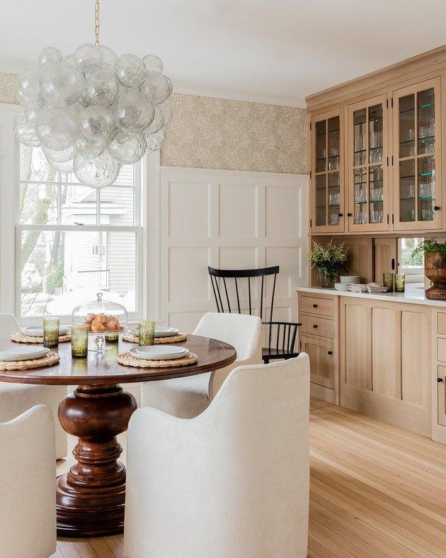 tall dining room wainscoting in farmhouse with floral wallpaper and built-in cabinetry