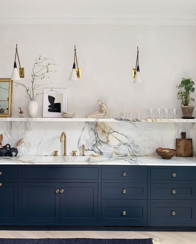 navy blue kitchen color idea with blue cabinets and marble countertop and backsplash