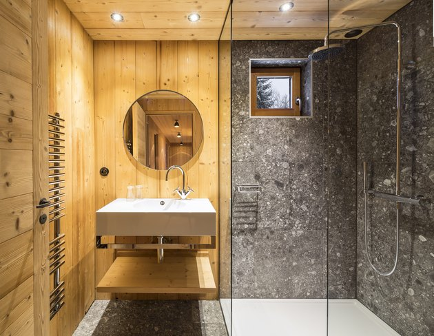 rustic shower idea with stone tile walls that balance the wood walls and ceiling