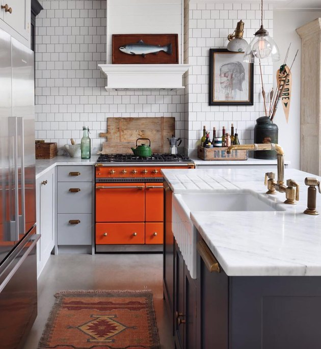 Red oven in kitchen with marble countertops and farmhouse sink.