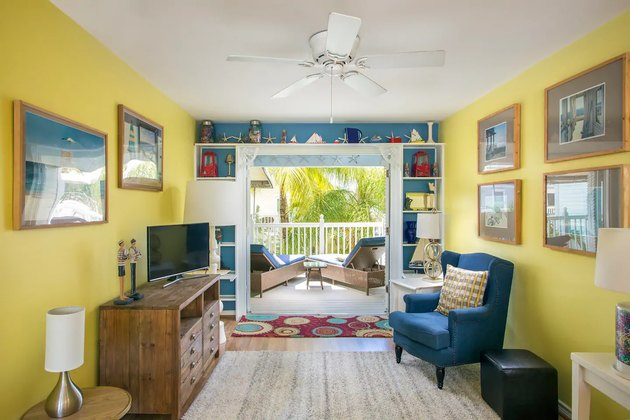 living room space with yellow walls and blue chair
