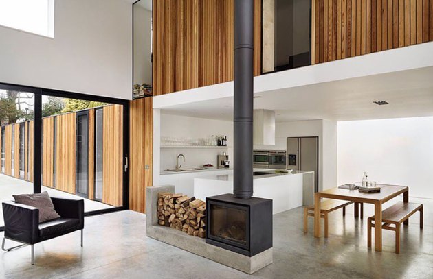 modern minimal living room and dining room with wood stove fireplace