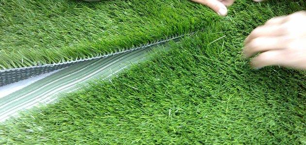 Creating an artificial turf seam.