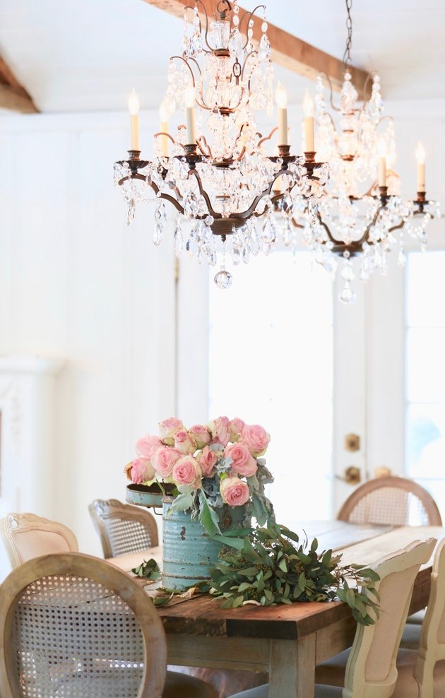 French country dining room with crystal chandeliers above rustic table