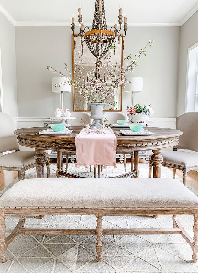 French country dining room idea with round table and chandelier