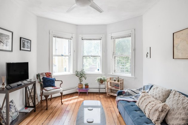 living room space with three windows and light blue couch