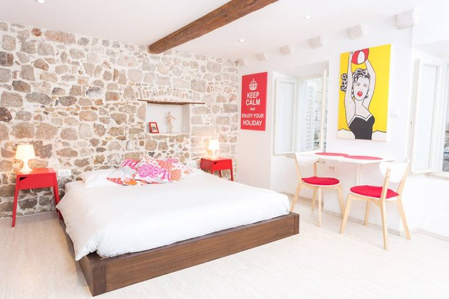 bedroom with brick wall and red furniture