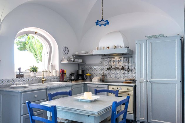 kitchen space with blue chairs, blue cabinets and blue lighting fixture