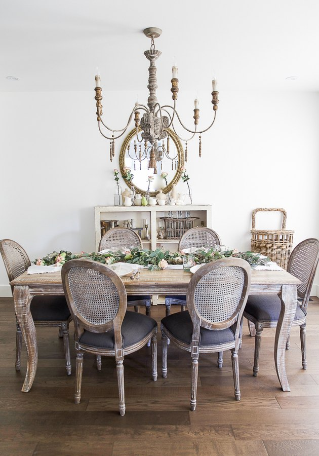 French country dining room with vintage style chairs and distressed table with chandelier above