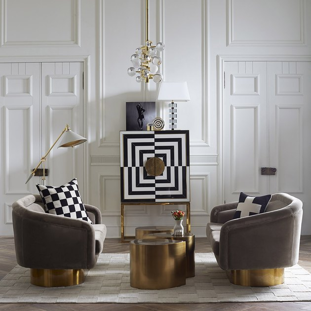 two gray chairs with gold bottoms and gold coffee table