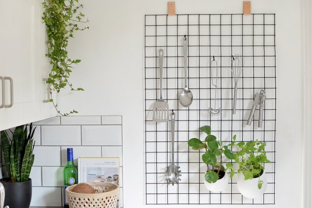 Grid wall organizer with kitchen utensils.