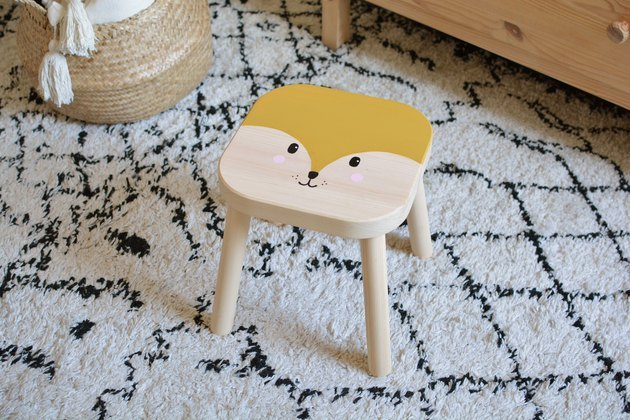 IKEA stool painted with an animal face in bedroom.