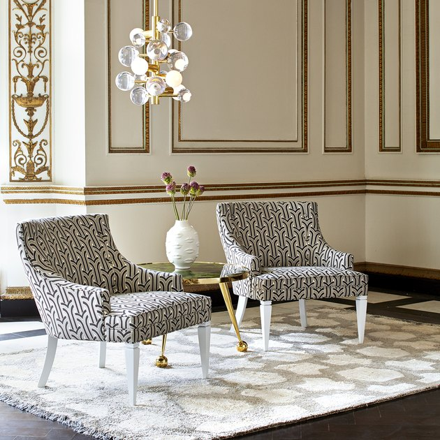 two patterned chairs with chandelier and white vase nearby