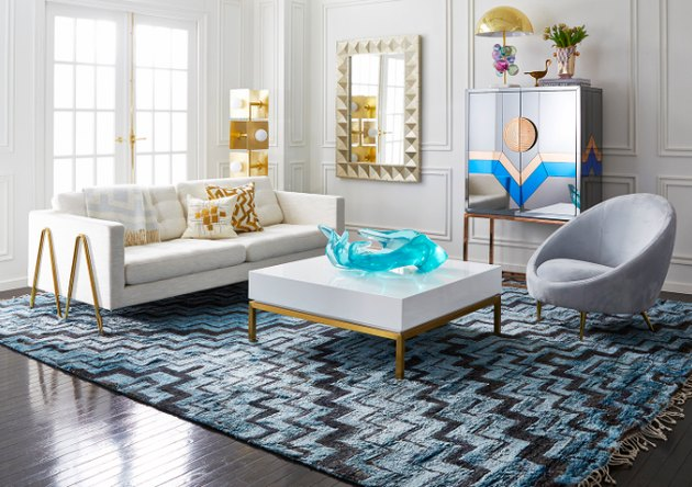 living room space with white couch, gray chair, and white coffee table with gold legs
