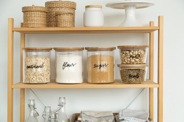 Bookshelf pantry with glass containers and baskets.