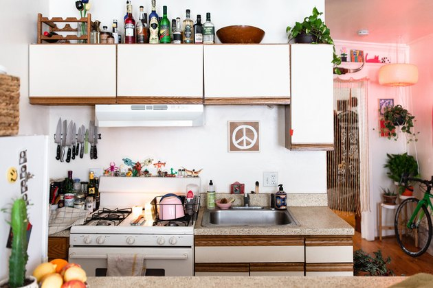 kitchen with white cabinets and liquor  bottles atop them