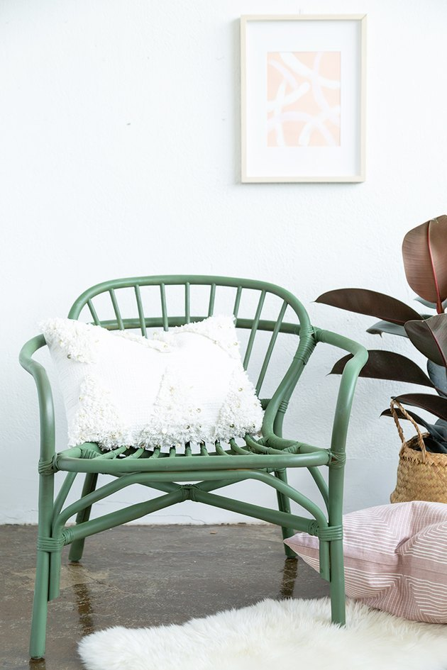 Green rattan chair with white pillow on sheepskin rug.