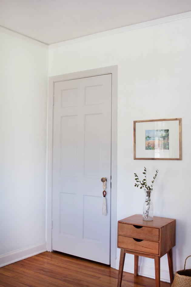 Door painted putty color, white walls, and wood side table with plant.