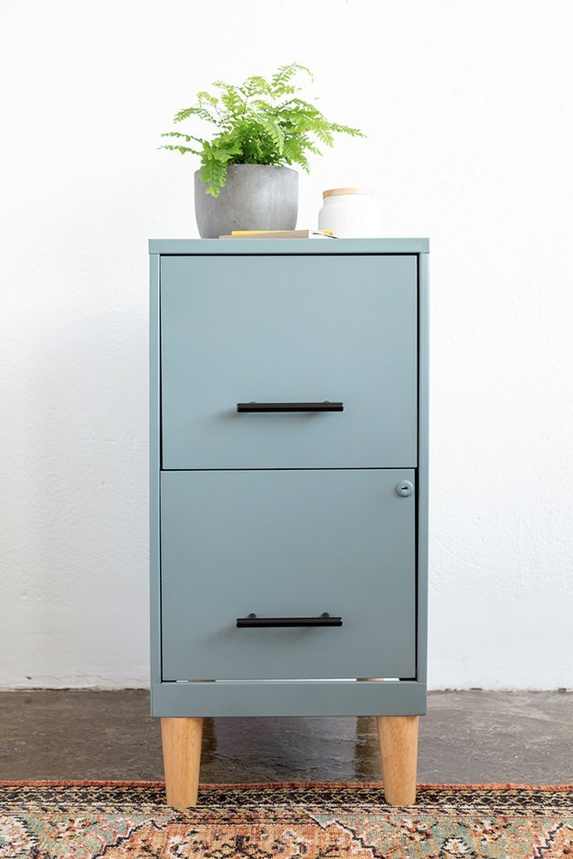Teal colored filing cabinet with wood legs on rug with plant on top.