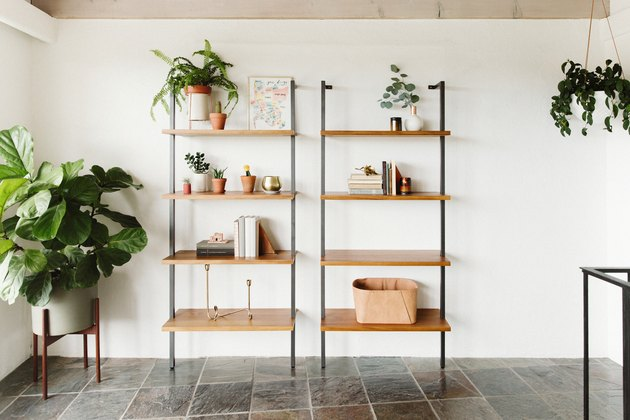 focus on open bookshelves in a tiled room with plants