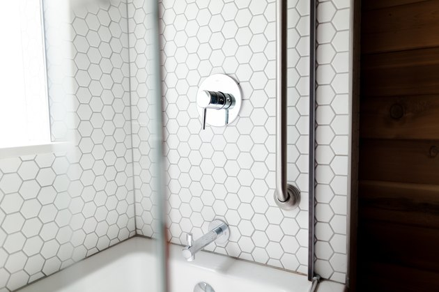 white hexagon tile shower, silver faucet and faucet handle, glass shower door