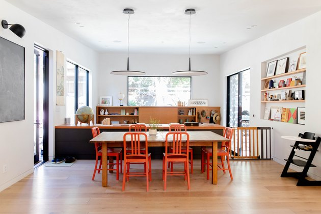 open dining room with orange chairs, pendant lamps, hardwood floors
