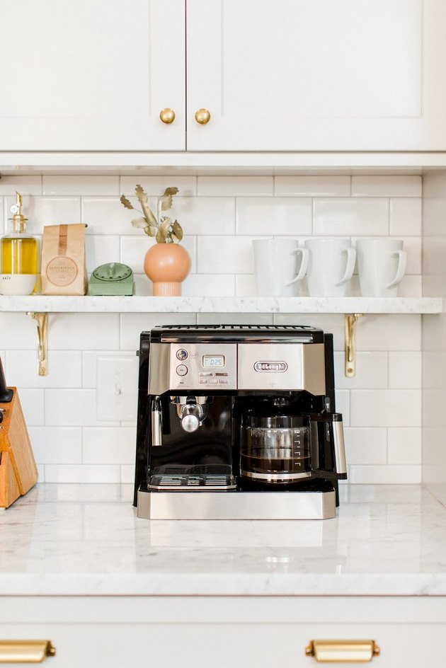 Farmhouse coffee bar with white subway tile, open marble shelf, and coffee maker