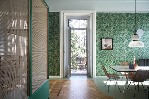 Green, edge-like Fornasetti wallpaper from Cole & Son in dining room.