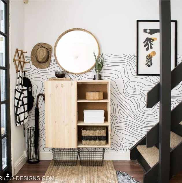 Entryway with mirror and wavy wallpaper.