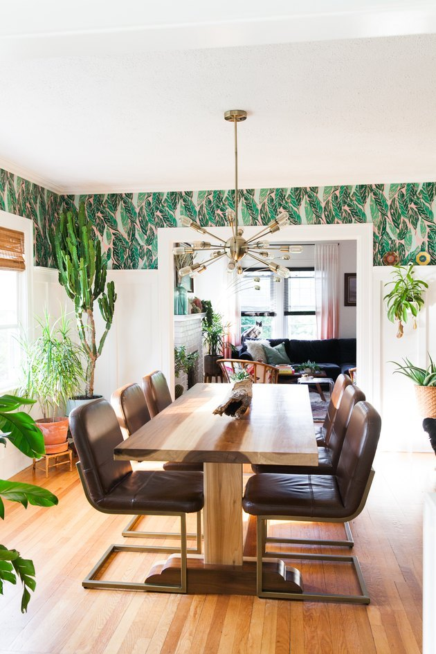 Tropical wallpaper in dining room with leather chairs and wood table.