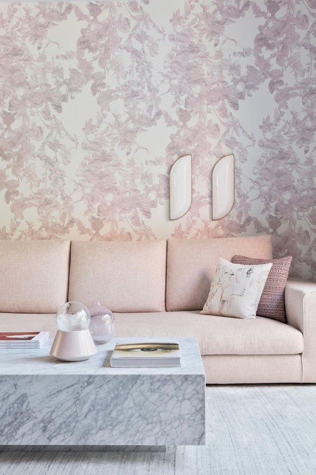Wall sconce on floral wallpaper over pink couch.