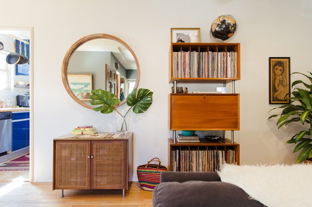 living room with bookshelves, round mirror, small credenza, view to blue cabinets in kitchen