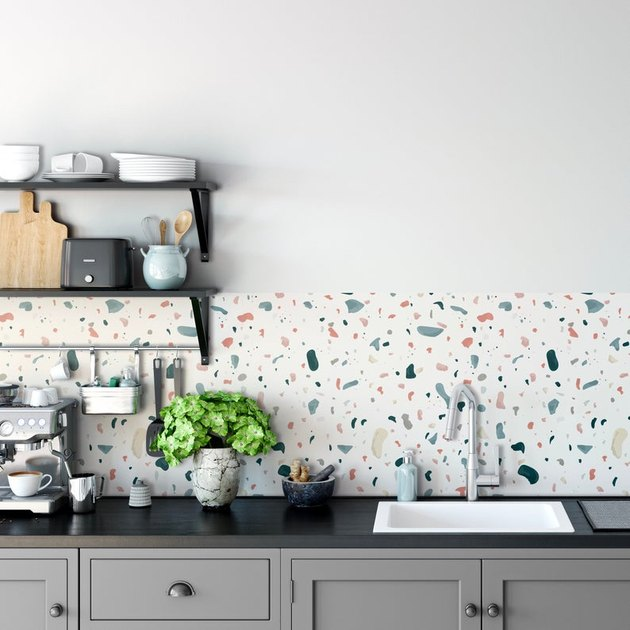 kitchen wallpaper backsplash idea with terrazzo and black countertop