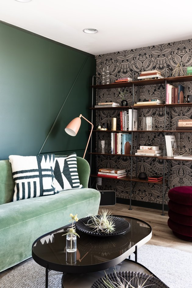 Home den/library with damask-like wallpaper and green velvet couch