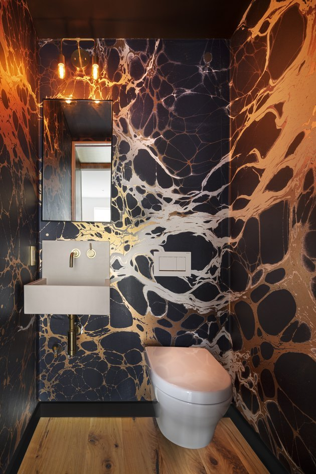 Powder room with bold patterned wallpaper in silver and black.