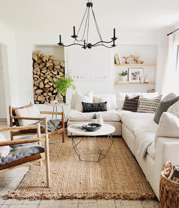 rustic living room idea with iron chandelier and stacked wood logs