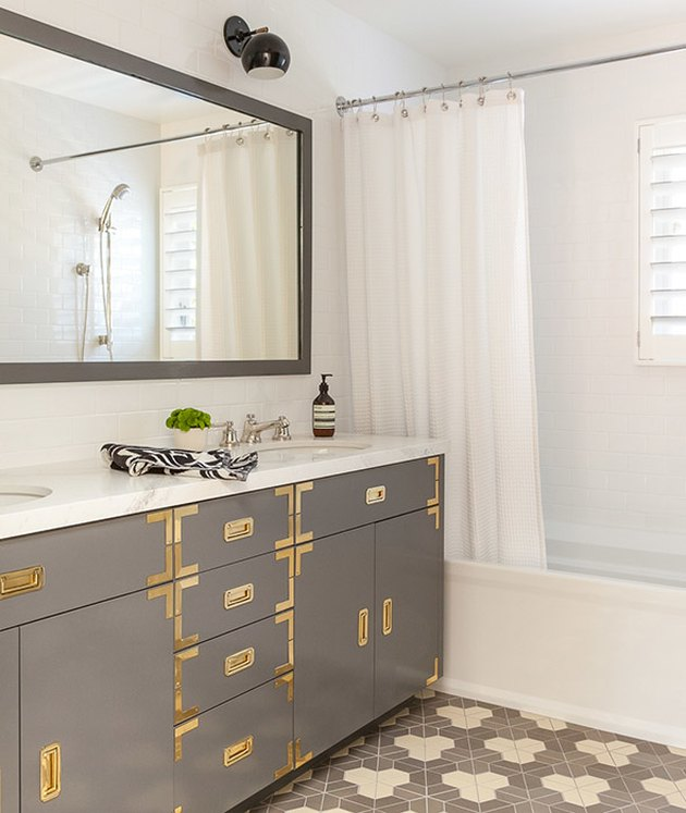 shower window idea with shutters and campaign bathroom vanity with brass hardware