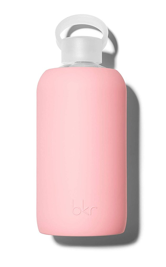 glass water bottle with pink silicone sleeve and white cap