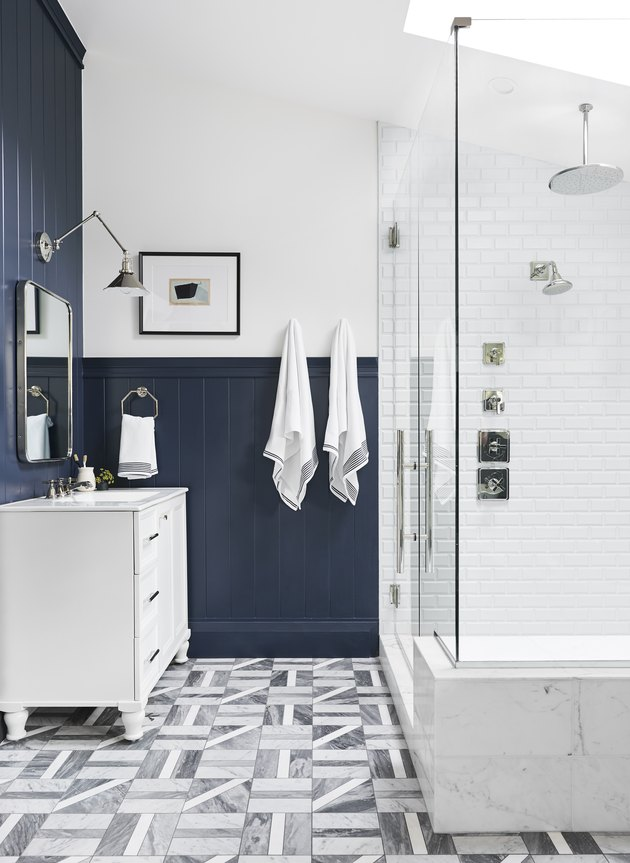 chrome rain showerhead in white and blue bathroom