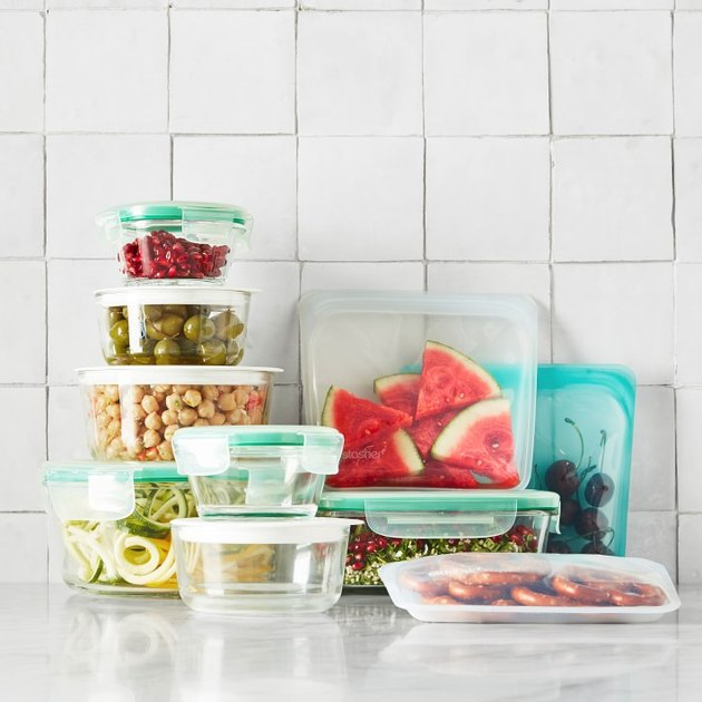 glass food storage containers stacked with reusable sandwich bags on a white counter