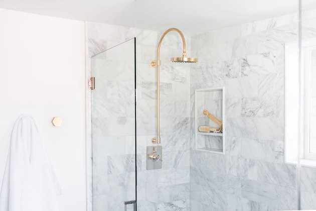 gold rain showerhead in marble shower