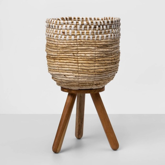 natural and white woven planter on wood stand