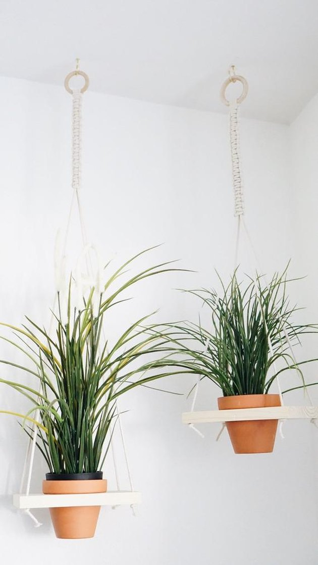 Pair of small hanging macrame planter holders with blonde wood base