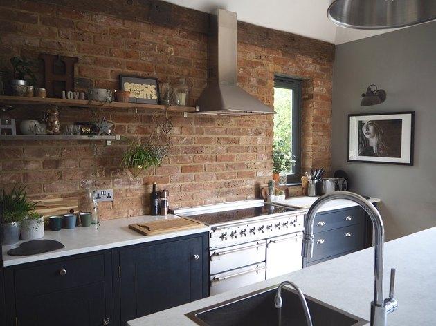 navy blue kitchen with brick backsplash