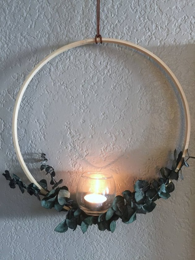 Minimal hanging wooden wreath with spray of foliage and candle holder at the bottom